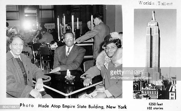 African American man and two women in a photograph taken at the top of the Empire State Building a tourist souvenir showing the man and women sitting...