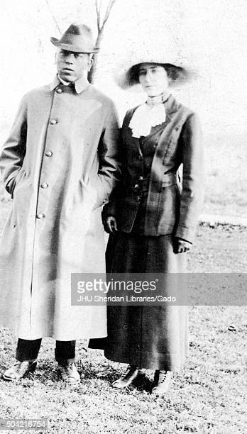 African American man and woman standing on the lawn and posing for a photograph wearing cold weather clothing the man with his hands in pocket woman...
