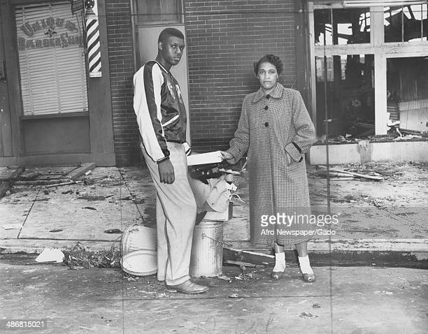 African American man and women place the destroyed remains of the barber shop into a trash can amidst debris and broken windows following a fire at...