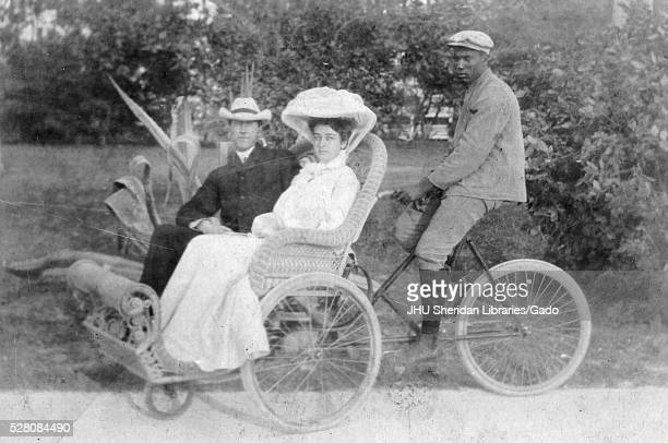 African American man bicycling carriage carrying white man and white woman African American man wearing dark suit with cap white woman wearing light...
