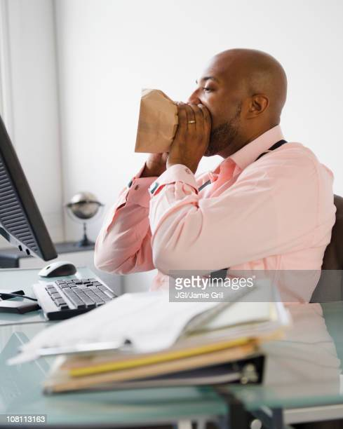 african american man breathing into paper bag - fainting stock pictures, royalty-free photos & images