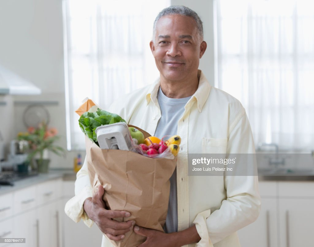 African American man carrying bag of groceries in kitchen : Foto stock