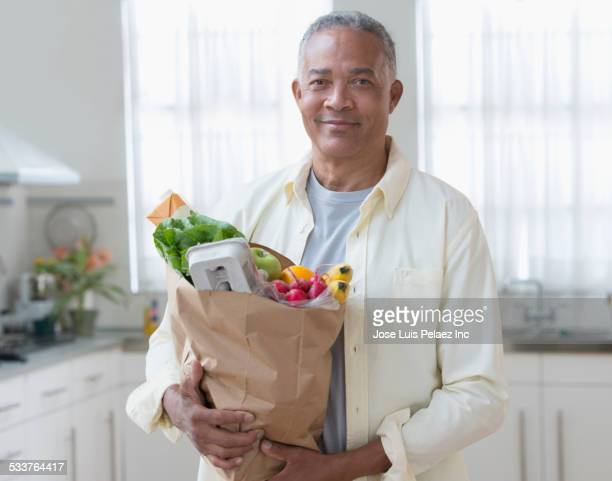African American man carrying bag of groceries in kitchen