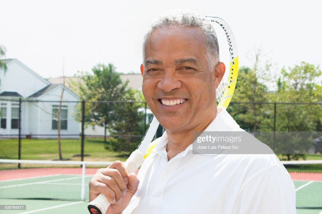 African American man carrying racket on tennis court : Foto stock