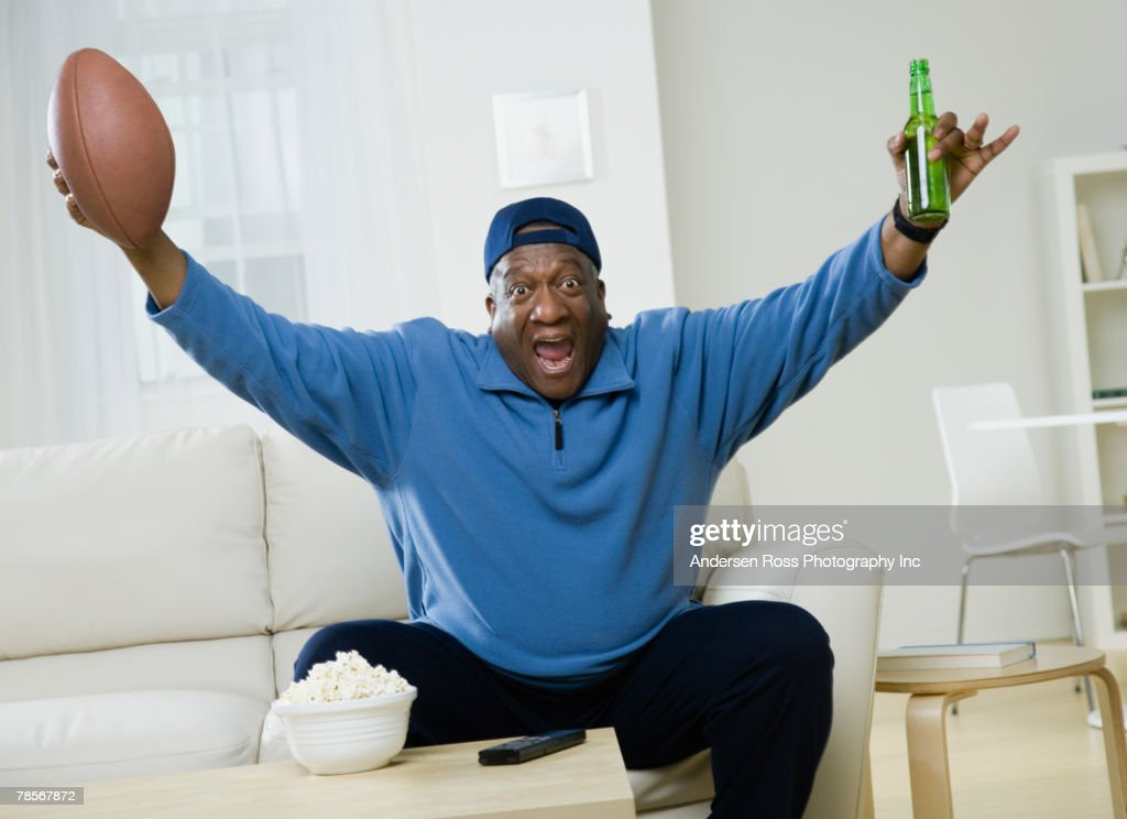 African American man cheering with football and beer : Stock Photo