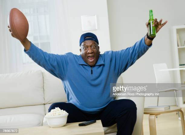 african american man cheering with football and beer - man cave stock pictures, royalty-free photos & images