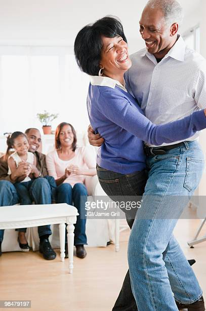 African American man dancing with wife in living room