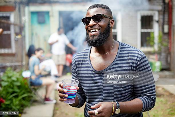 african american man drinking at backyard barbecue - black people partying stock photos and pictures