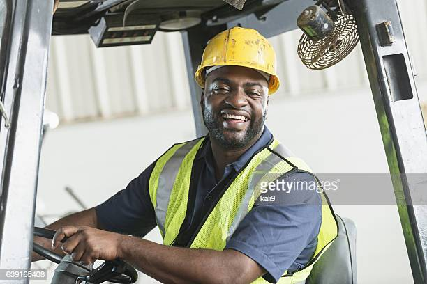 African American man driving a forklift