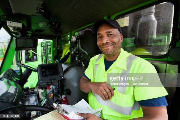 african american man driving garbage truck - garbage truck stock pictures, royalty-free photos & images