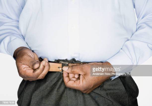 african american man fastening belt - tighten stock photos and pictures