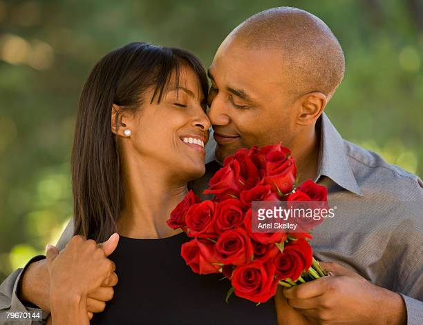 african american man giving flowers to wife - valentines african american stock pictures, royalty-free photos & images