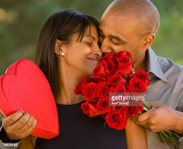 african american man giving valentine's day gifts to wife - valentines african american stock pictures, royalty-free photos & images