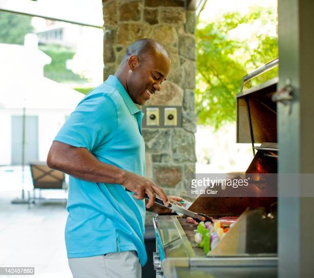 African American man grilling food on barbecue