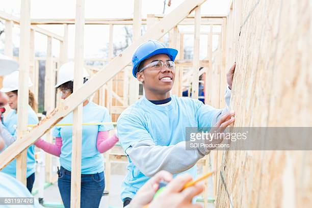 African American man helps build charity home