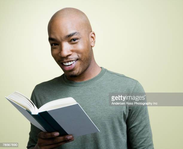 african american man holding book - man holding book stock pictures, royalty-free photos & images