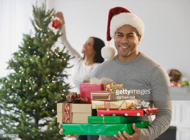 African American man holding Christmas gifts by tree
