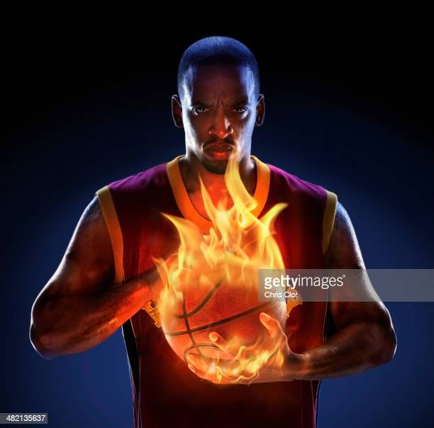 African American man holding flaming basketball