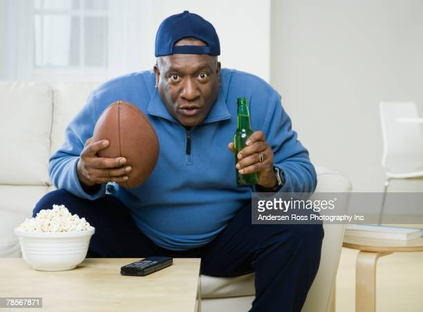 african american man holding football and beer - man cave stock pictures, royalty-free photos & images