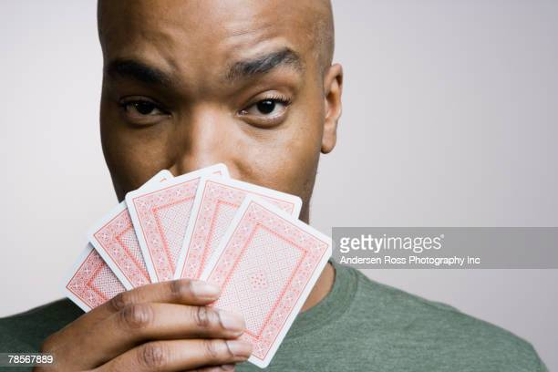 African American man holding playing cards