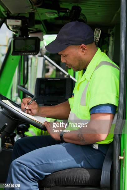 african american man in garbage truck writing on clipboard - garbage truck stock pictures, royalty-free photos & images