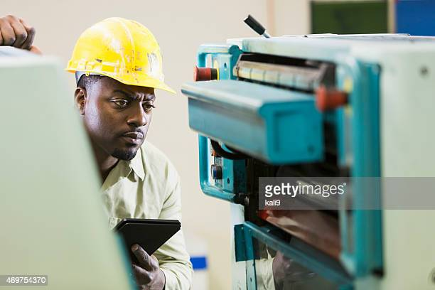 African American man in print shop with digital tablet