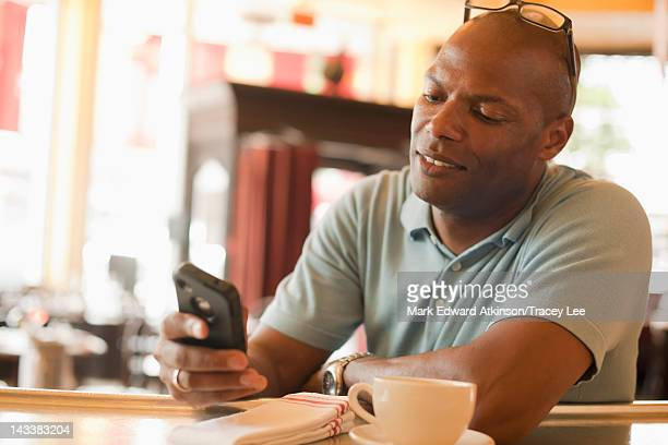 African American man in restaurant text messaging on cell phone