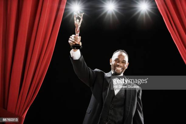 African American man in tuxedo holding trophy onstage