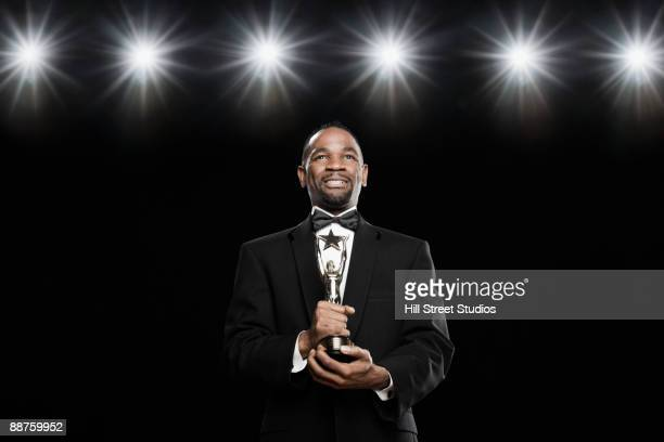 african american man in tuxedo holding trophy - awards ceremony stock pictures, royalty-free photos & images