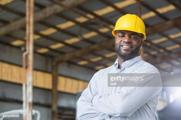 African American man in warehouse wearing hardhat