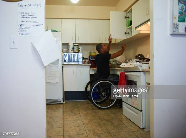 African American man in wheelchair opening cabinet in domestic kitchen