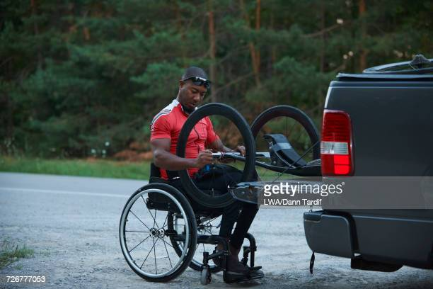African American man in wheelchair removing handcycle from truck