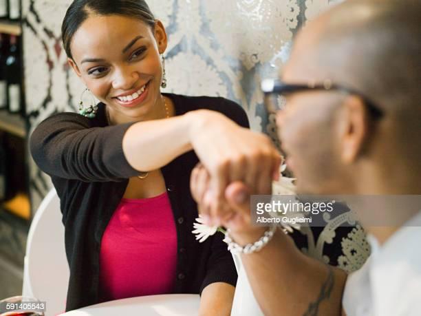 African American man kissing hand of girlfriend in restaurant