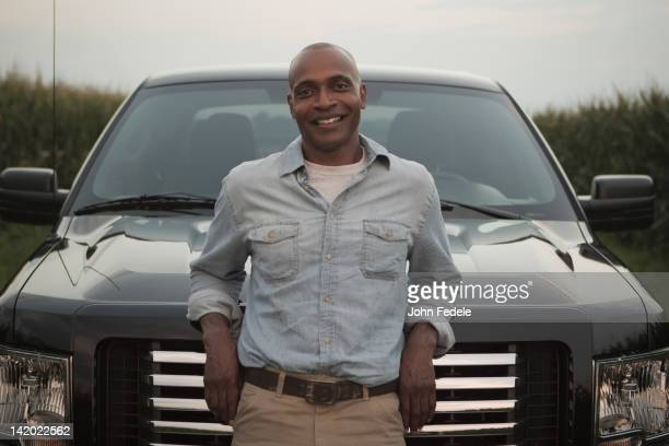 African American man leaning on hood of car