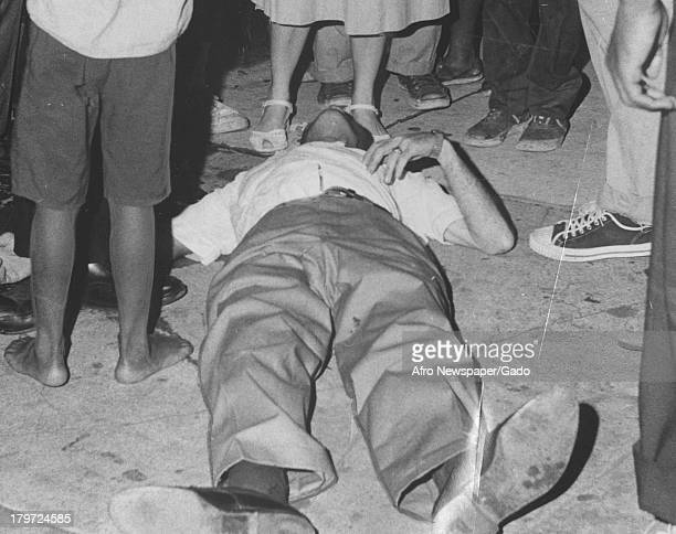 African American man lies on the ground during a riot, Baltimore, Maryland, August 1966.