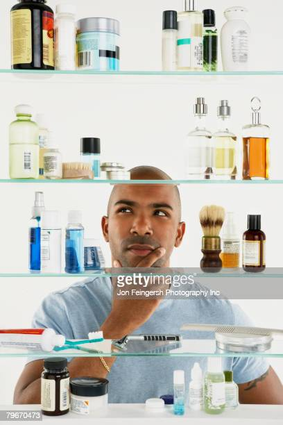 african american man looking in medicine cabinet - medicine cabinet stock pictures, royalty-free photos & images