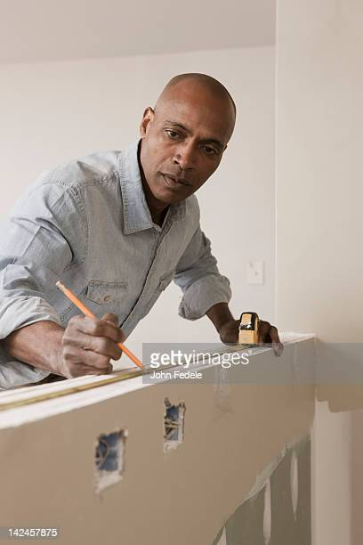 African American man measuring wall in unfinished room