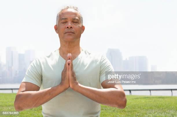 African American man meditating in urban park
