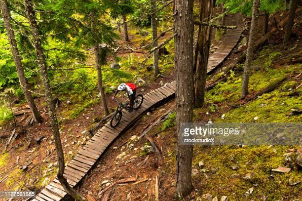 african american man mountain biking through a forest - mountain bike stock pictures, royalty-free photos & images