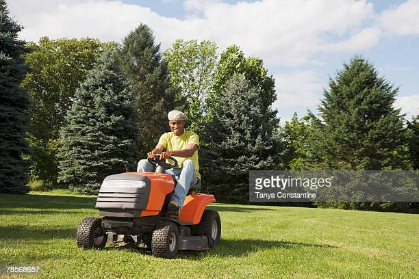 african american man mowing lawn - tanya constantine stock pictures, royalty-free photos & images