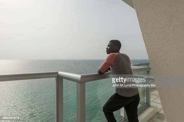 african american man overlooking ocean from balcony - 見渡す ストックフォトと画像