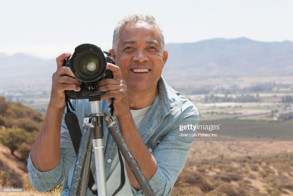 African American man photographing in scenic remote landscape : Foto stock