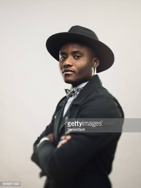 African american man posing in black jacket and hat