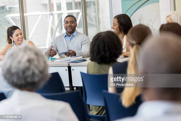 african american man presents paper on small business ventures - panel discussion stock pictures, royalty-free photos & images