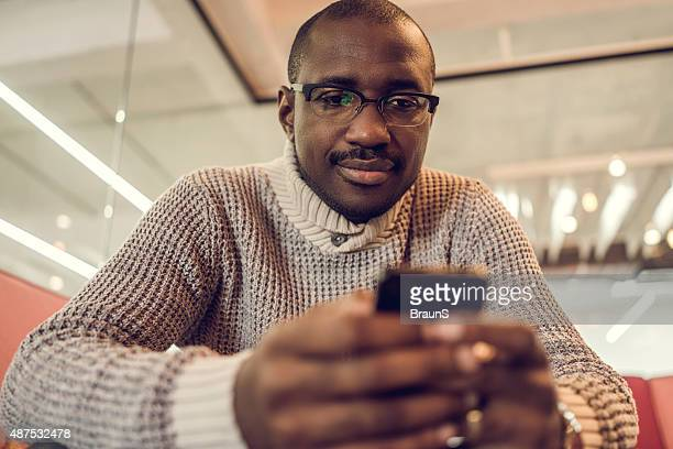 African American man reading a text message on smart phone.