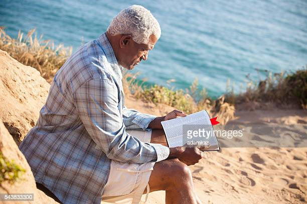 african american man reading bible - bible photos stock pictures, royalty-free photos & images