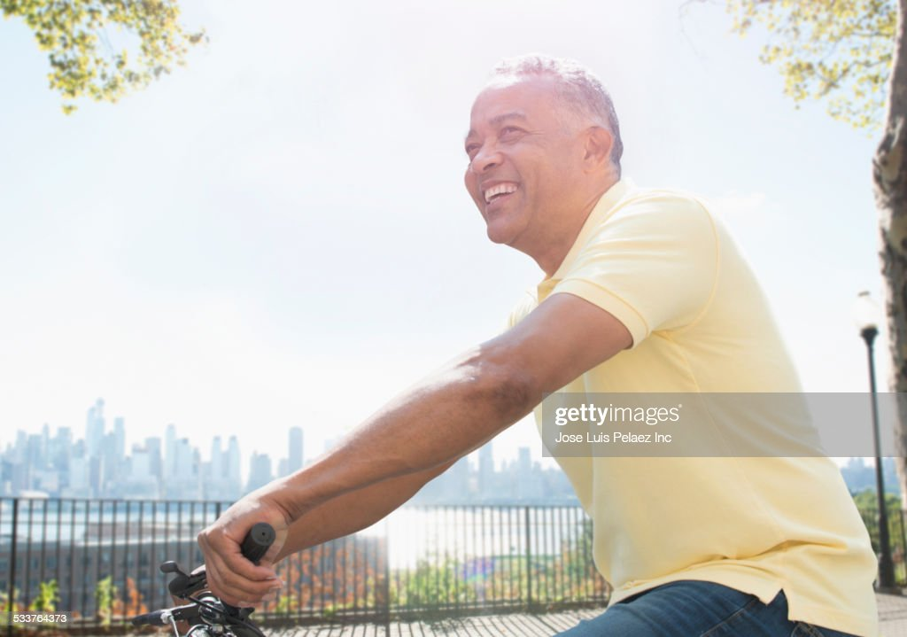 African American man riding bicycle in city park : Foto stock