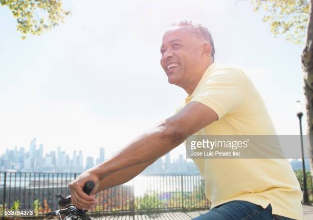 African American man riding bicycle in city park