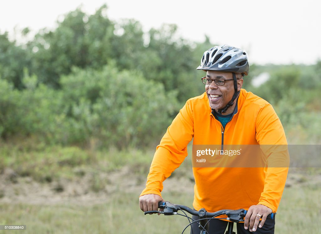 African American man riding bike in park : Stock Photo