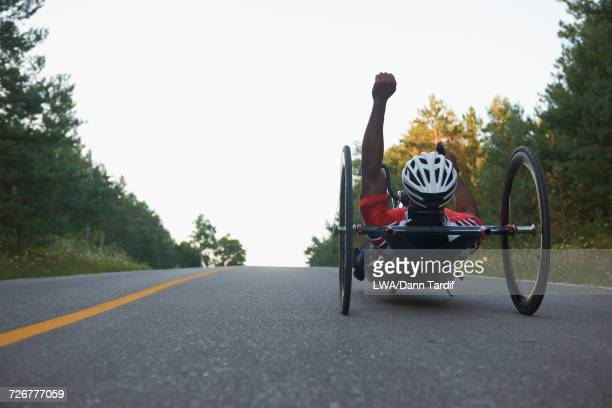 African American man riding handcycle and celebrating